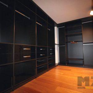 Большая гардеробная с закрытыми шкафами для хранения в темном цвете