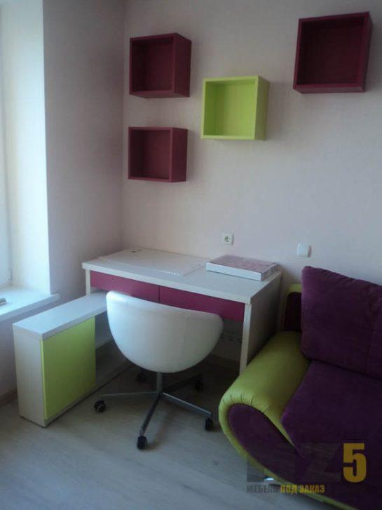 Маленький белый компьютерный стол с розовыми выдвижными ящиками, салатовой приставной тумбой и бордовыми декоративными полками