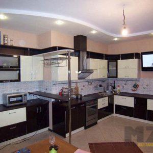 Двухцветная кухня с глянцевыми фасадами угловой конфигурации