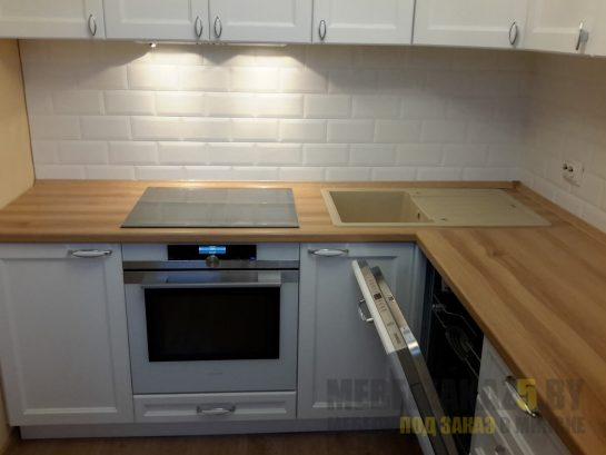 Угловая современная кухня с деревянной столешницей и встроенной техникой
