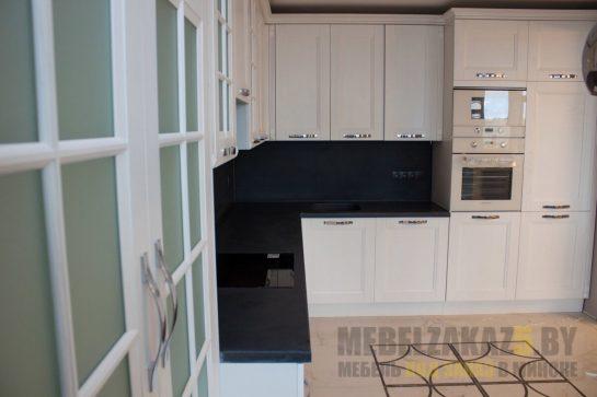 Белая угловая кухня с черным фартуком и столешницей в современном стиле