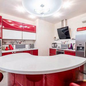 Глянцевая красно-белая кухня с круглым островом и белой столешницы