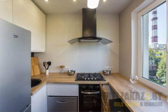 Маленькая п-образная кухня с деревянной столешницей и встроенной техникой